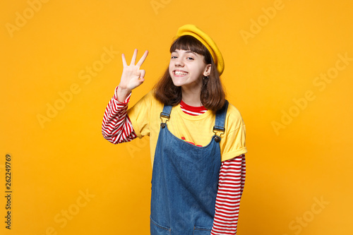 Cuadros en Lienzo  Portrait of smiling girl teenager in french beret, denim sundress showing OK gesture isolated on yellow wall background in studio