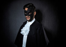 Young Attractive Man Wearing A Dark Mask, Dressed In A 10's-20's Style With A White Shirt And Black Cape
