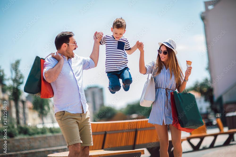 Fototapeta Happy family having fun outdoor after shopping