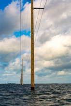 Vertical Image Of Florida Keys Power Powerlines Moving From Right To Left Through The Shallows Of Key West Florida With Clouds In The Blue Sky