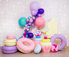 Set Of Huge Artificial Sweets And Pastry Decorations Over White Brick Wall