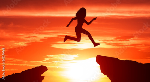 Poster de jardin Rouge Reach the goal. Silhouette of woman jumping over the mountains
