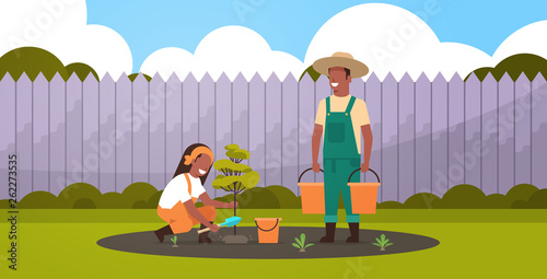 Foto couple farmers planting young tree african american man holding water buckets wo