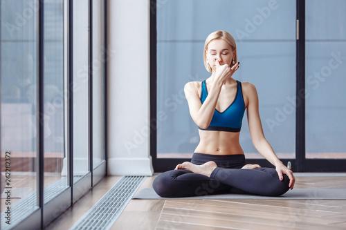 Obraz Charming slim woman yoga instructor doing padmasana basic yoga posture for pranayama in the spacious hall. The concept of breath control relaxation and meditation - fototapety do salonu