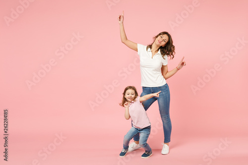 Woman in light clothes have fun with cute child baby girl. Mother, little kid daughter isolated on pastel pink wall background, studio portrait. Mother's Day, love family, parenthood childhood concept - 262284185