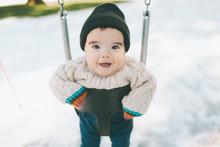 A Baby In A Swing In Winter