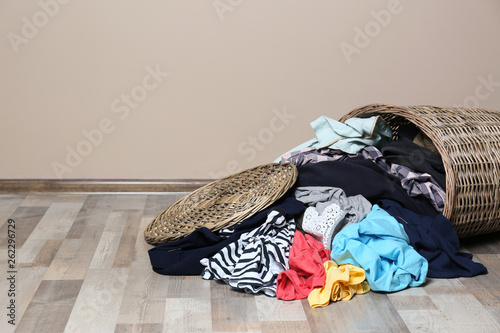Dirty clothes scattered from laundry basket on floor indoors Fototapeta