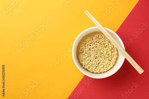 Fotografía  Cup of instant noodles with chopsticks on color background, top view