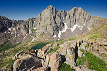 Marmot Sits On Rocks On A Saddle Of Humboldt Peak Wtih Crestone Needle And Crestone Peak In Distance Rising Above South Colony Lake, Colorado