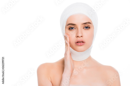 naked girl with bandaged head touching face after plastic surgery isolated on wh Canvas Print
