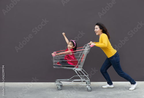 Fotografía happy mom and kid go shopping cart together.