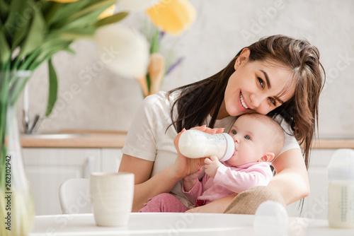 Woman feeding newborn with formula in a bottle. Canvas Print