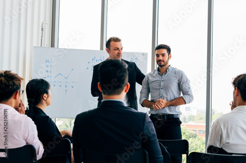 Fotografía  Contemporary businessmen standing in light office room and presenting new projec