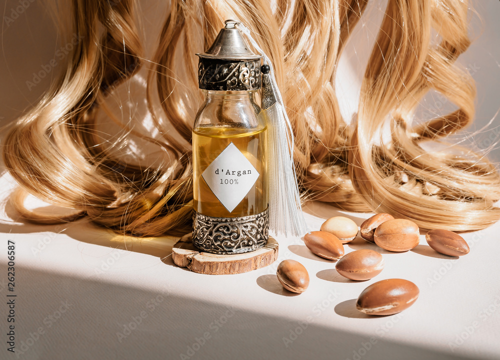 Fototapety, obrazy: Curls of golden hair and decorative bottle with iron embossed in traditional Moroccan style with precious Moroccan argan oil and nuts ander natural lighting of sun with hadows frame