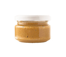 Side View Of Glass Jar With Nut Butter, Hummus Or Sesame Paste Tahini Isolated On White Background