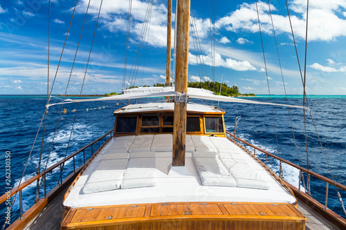 luxury sailing boat yacht in front of tropical paradise maldives island resort with coral reef and blue ocean water tourism background
