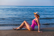 A beautiful pose of a girl in a pink swimsuit sitting on the san