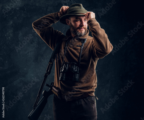 Fotografia Bearded hunter with rifle and binoculars corrects his hat and looking sideways