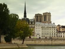 Panorama Brzegu Sekwany W Paryżu Z Widokiem Na Zabytkowe Budynki, Za Nimi Dwie Wieże I Iglica Katedry Notre Dame Na Tle Zachmurzonego Nieba, Stylizowany Na Akwarelę