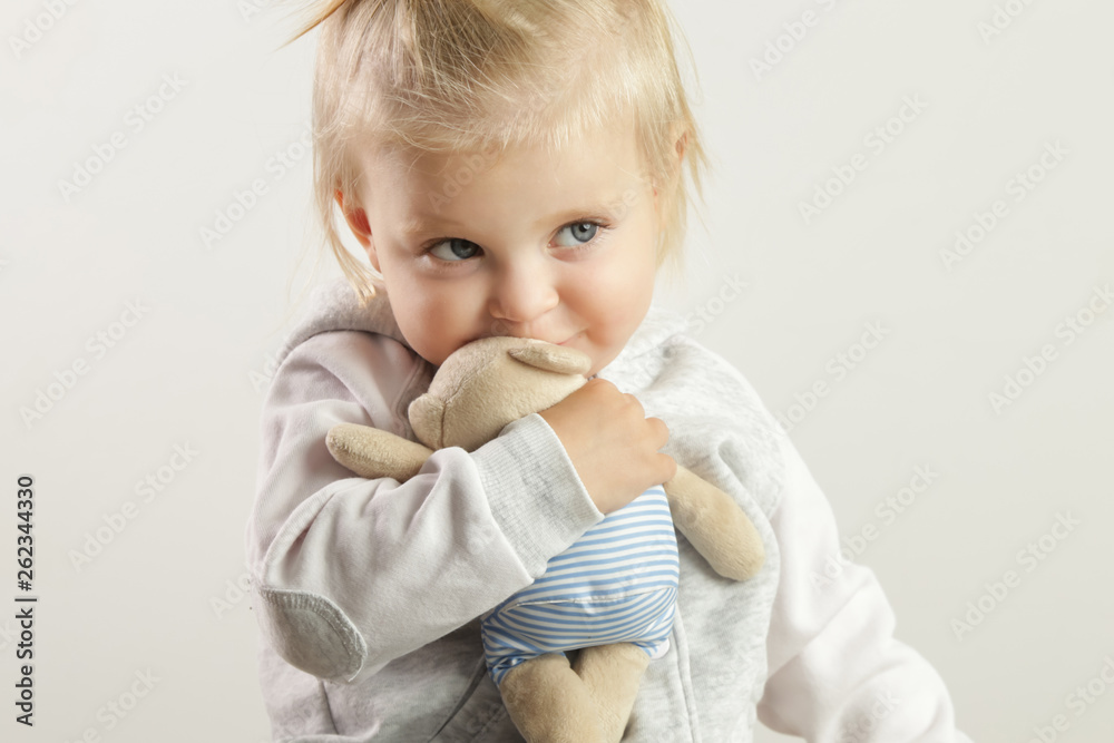 Fototapeta An adorable baby girl hugging with her favorite soft toy