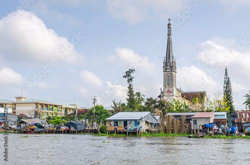 Fotografija  One of the banks of the Mekong river with the Cathedral of Cai Be, a river-land