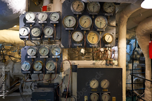 Fototapeta Control panel with vintage manometers, pressure gauges and thermometers in boiler room of steam powered war ship or batte ship from world war two served in Royal british navy in north atlantic ocean