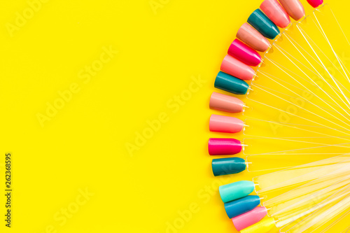 Fotomural palette for nail artist work on yellow desk background top view mock up