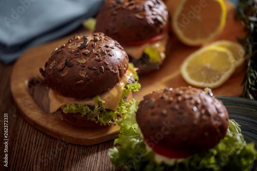 Dark burger with grain bread on dark ceramic plate, salad, rosemary and lemon