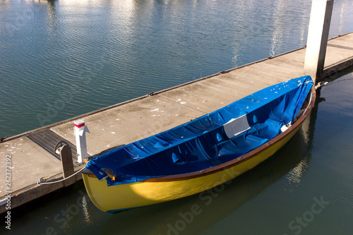 blue and yellow rowboat by a pier on the bay in harbor
