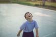 Outdoor portrait of a happy Asian student kid in school uniform smiling.