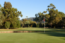 Golf Flag On Green Looking Back Up Fairway With Gum Trees And Blue Sky Background At Bright Golf Course In Victoria Australia