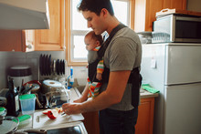 Young Caucasian Father With Newborn Baby In Carrier Preparing Lunch. Man Parent Carrying Child Standing In Kitchen Making Food. Authentic Lifestyle Candid Real Moment. Single Dad Family Life Concept