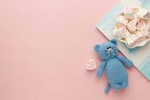 A Small Knitted Baby Toy-cat, Nitebook And Sweetness Marshmallow On Pink Pastel Background, Flat Lay, Top View, Copy Space