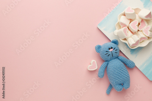 Obraz A small knitted baby toy-cat, nitebook and sweetness marshmallow on pink pastel background, flat lay, top view, copy space - fototapety do salonu