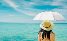 Back View Of Asian Woman Wear Swimsuit And Hand Hold White Umbrella At Tropical Beach On Sunny Day With Beautiful Blue Sky And White Clouds. Woman Travel On Summer Vacation. Summer Vibes. Happy Girl.