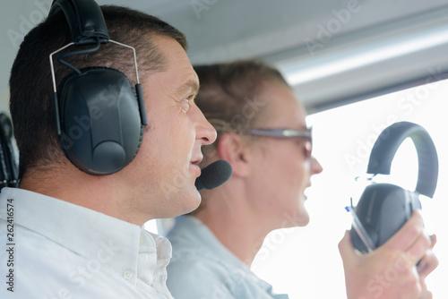 close view of pilot wearing headset with female companion Tapéta, Fotótapéta