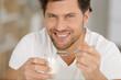 smiling young man eating yogurt