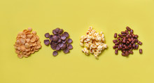 Various Cereals Cornflakes Snack And Popcorn Pile On Yellow Background Top View For Breakfast