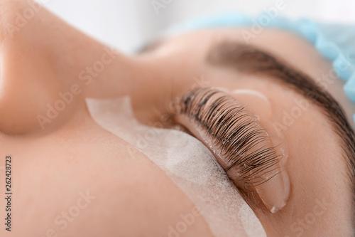 Photo  Young woman undergoing procedure of eyelashes lamination in beauty salon, closeu