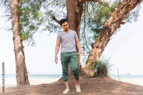 Fotografía  Man is standing under the pine tree on the beach