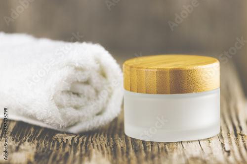 Photo  Ein Handtuch neben einer Cremedose vor Holz-Hintergrund.