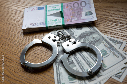 Fotografie, Tablou  Handcuffs and money closeup, consept of money crimes
