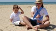 A happy mother and her son are sitting on a sandy beach on a sunny summer day and playing with a toy plane, in slow motion