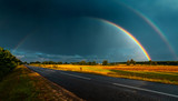 Fototapeta Tęcza - Double rainbow over the highway in darkly blue sky after a rain