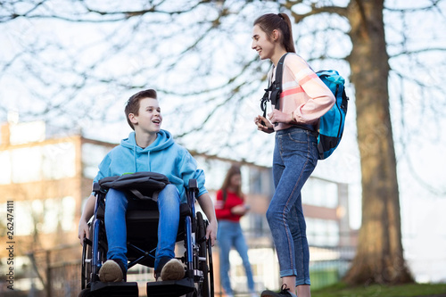 Teenage Boy In Wheelchair Talking With Female Friend As They Leave High School Canvas Print