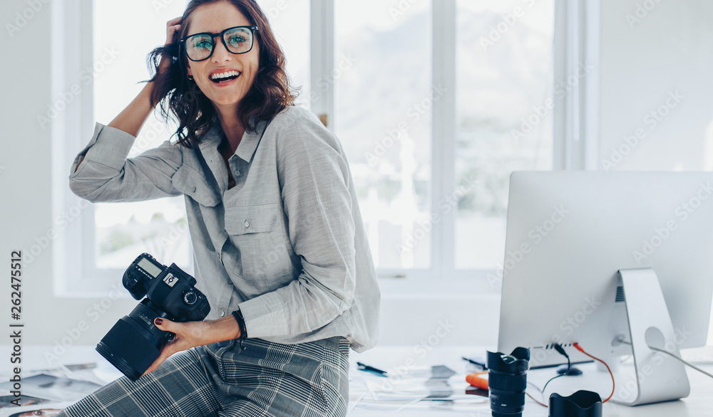 Fototapety, obrazy: Smiling female photographer in office