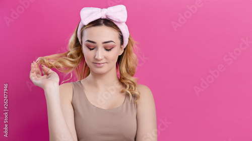 Valokuva portrait of a beautiful girl woman in a headband for make up on a studio backgro