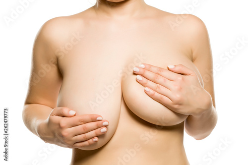 Fotografía  A woman with univen big breasts on white background
