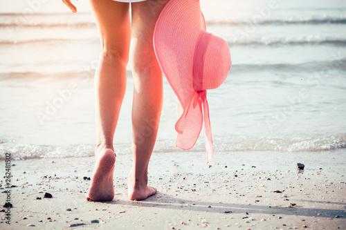 Foto auf Gartenposter Weiß Foot of woman walking on the beach with holding pink hat