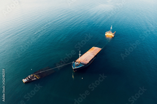 Photo Stands Shipwreck Sunken cargo ship near Crimean seaside, aerial view from drone. Shipwreck vessel with nose of ship above sea water